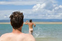 Man sitting on a lake shore watching another man run naked into the lake