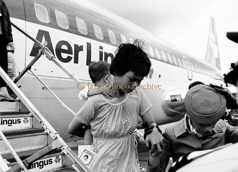 A young Vietnamese woman and her child being assisted from the aircraft by an Aer Lingus hostess. As part of a UNHCR initiative, Ireland agreed to take some of the  Vietnamese (boat people) refugees. A temporary refugee centre was set up in the grounds of Blanchardstown Hospital to accommodate the families, from where they were assimilated into the community. Refugees Arriving<br /> 09/08/1979