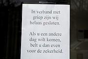 In Utrecht hangt bij een winkel een briefje aan de deur dat ze in verband met griep gesloten zijn.