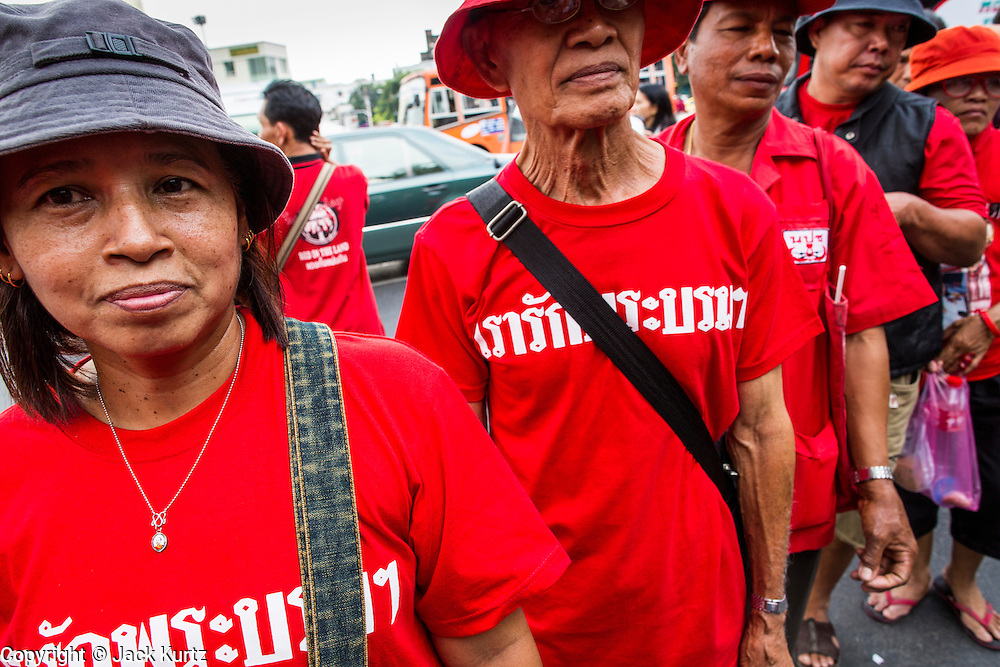 "10 DECEMBER 2012 - BANGKOK, THAILAND:  Thai Red Shirt protestors line up on Ratchadamnoen Avenue in Bangkok Monday. The Thai government announced on Monday, which is Constitution Day in Thailand, that will speed up its campaign to write a new charter. December 10 marks passage of the first permanent constitution in 1932 and Thailand's transition from an absolute monarchy to a constitutional monarchy. Several thousand ""Red Shirts,"" supporters of ousted and exiled Prime Minister Thaksin Shinawatra, motorcaded through the city, stopping at government offices and the offices of the Pheu Thai ruling party to present demands for a new charter.        PHOTO BY JACK KURTZ"