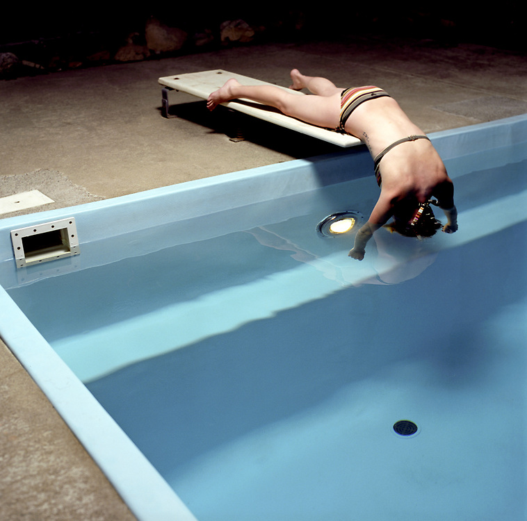 Woman 30's lying on diving board dipping head in residential swimming pool