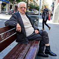 Un hombre mayor descansa, en la calle Gran de Gracia, mientras fuma su pipa en Barcelona, España. A senior man rests, while smoking his pipe, on Gran de Gracia street in Barcelona, Spain