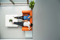 Two people reclining on couch in reception room view from above