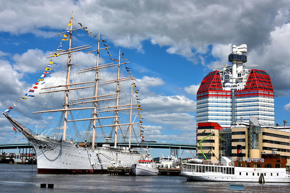 Lipstick Building and Barken Viking Ship in Gothenburg, Sweden <br /> Side-by-side at Gothenburg&rsquo;s harbor are two of its famous landmarks.  On the left is the Barken Viking, the Nordic countries&rsquo; largest sailing ship at 387 feet. The four-masted barque was launched in 1906 as part of Denmark&rsquo;s merchant fleet, decommissioned in 1950 and is now a hotel and restaurant.  On the right is the distinctive Skanska Skyscraper. Although it is formally called Lilla Bommen, its red upper floors earned it the nickname The Lipstick Building.  Near the top of L&auml;ppstiftet&rsquo;s 282 feet height is the G&ouml;theborgs Utkiken observation deck.