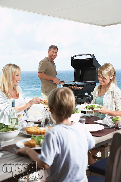 Family sitting around table outside eating Barbecue father standing at grill grilling