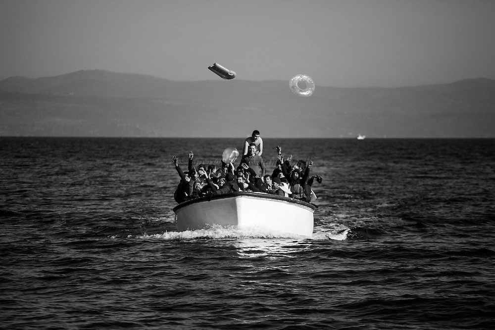 Refugees and migrants riding a dinghy reach the shores of the Greek island of Lesbos after crossing the Aegean Sea from Turkey on November 13, 2015.