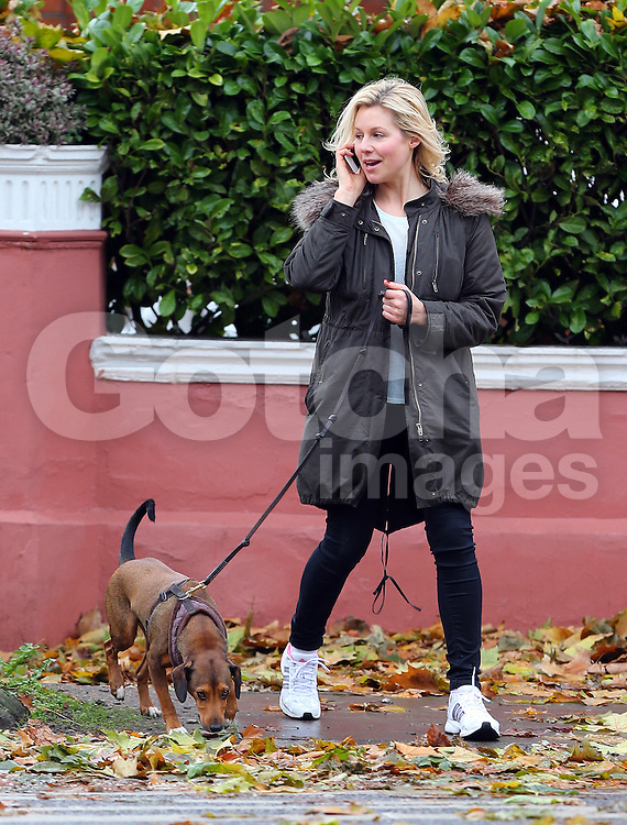 English actress, television personality, former glamour model and nurse, Abi Titmuss plays hide and seek as she walks her dog in north London, UK. 20/11/2012<br />