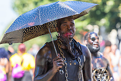 London, August 27 2017. Smeared in oily liquid, a man with an umbrella makes his way along Ladbroke Grove as Family Day of the Notting Hill Carnival gets underway. The Notting Hill Carnival is Europe's biggest street party held over two days of the bank holiday weekend, attracting over a million people. © Paul Davey.