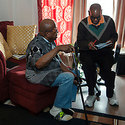 Mr. Johnson, left, and his caretaker Reggie Griffin look over Mr. Johnson's checkbook and bank balance. John E. Johnson, who is not eligible for medicaid, receives services for 12 hours per week through Illinois' Community Care Program. Johnson worries his services will be cut if the state transition seniors like him to a new program. The state employs Reggie Griffin to help Johnson with daily chores so he is able to stay in his home, as opposed to going to an nursing home. <br /> Photography by Jose More