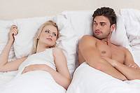 Angry young couple looking at each other in bed
