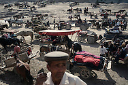 Donkey carts parked on a dried river bed during Kuqa weekly market. Southern Xinjiang is one of China's poorest region. Locals main source of income is farming and animals husbandry.