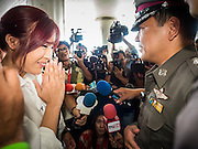 22 MAY 2015 - BANGKOK, THAILAND:   Anti-coup activist NATCHACAH KONG-UDOM  greets a Thai police officer at the start of an anti-coup protest in Bangkok. The Thai military seized power in a coup on May 22, 2014. There were small protests throughout Bangkok Friday to mark the first anniversary of the coup. Police arrested protestors at several locations. The most serious protest was at Bangkok Art and Culture Centre (BACC) where about 100 protestors, mostly students, faced off against police for several hours. Police made numerous arrests at the BACC protest.   PHOTO BY JACK KURTZ