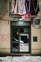 "NAPLES, ITALY - 12 SEPTEMBER 2018: The entrance of the Taverna del Buongustaio, a tavern in Naples, Italy, on September 12th 2018.<br /> <br /> Taverna del Buongustaio was founded in the 1930s by wine producer of the province of Caserta. Gaetano Aiese and his daughter Giusy have been managing the tavern since 1996. Customers of the Taverna are professors of the nearby University, students, merchants and employees of via Toledo, the commercial street right around the corner. Giusy and her father Gaetano decided to invest in the traditional Neapolitan cuisine. ""I learned cooking from my dad. And my dad learned cooking from his mother"", Giusy said."