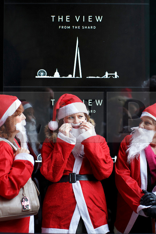 © licensed to London News Pictures. London, UK 15/12/2013. People dressed as Father Christmas queuing to experience The View from The Shard for free as the Shard offers complimentary access to the guests dressed in a full traditional Santa outfit to celebrate the skyscraper's first Christmas on Sunday, 15 December 2013. Photo credit: Tolga Akmen/LNP