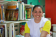 C&A volunteer, Daniele, photographed at the community library, Biblioteca Chocolatao, where she volunteers in Porte Alegre, Brazil.
