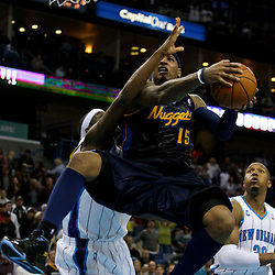 Dec 18, 2009; New Orleans, LA, USA;  Denver Nuggets forward Carmelo Anthony (15) is defended under the basket by New Orleans Hornets forward James Posey (left) during the second half at the New Orleans Arena. The Hornets defeated the Nuggets 98-92. Mandatory Credit: Derick E. Hingle-US PRESSWIRE