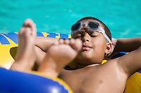 Boy (10-12) Relaxing on inflatable raft in swimming pool.