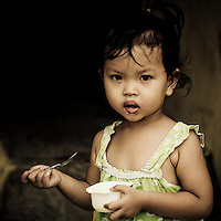 A little girl eats her yogurt with a spoon on a street in the Old Quarter of Hoi An, Vietnam, Southeast Asia,