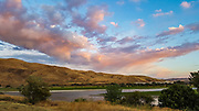 Sunset colors clouds over the Snake River, at Farewell Bend State Recreation Area in Baker County, Oregon, USA. Farewell Bend was the last stop on the Oregon Trail along the Snake River where travelers could rest and water and graze their animals before the trail turned north through more rugged country to follow the Burnt River. The park is 25 miles northwest of Ontario.