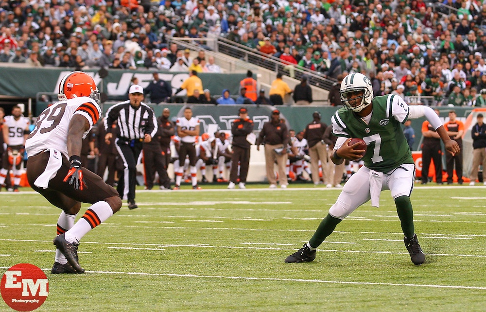 Dec 22, 2013; East Rutherford, NJ, USA; New York Jets quarterback Geno Smith (7) runs with the ball while being chased by Cleveland Browns free safety Tashaun Gipson (39) during the first half at MetLife Stadium.