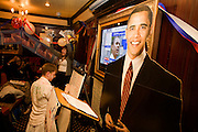 Democrat Party member keeps up with latest results with life-size cardboard cut-out of Barack Obama during 2008 elections