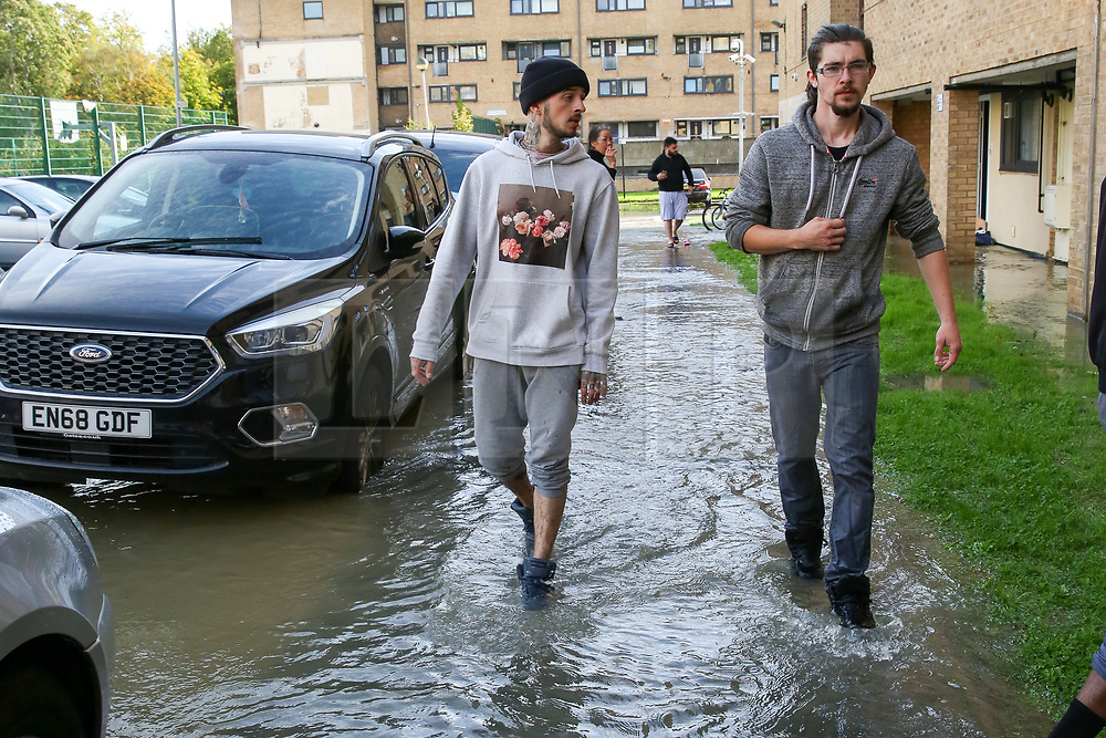 © Licensed to London News Pictures. 08/10/2019. London, UK. Residents walk through the water in Theobalds Court following a burst water main on Brownswood Road in Finsbury Park, north London. Photo credit: Dinendra Haria/LNP