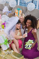 Bride with friends photographing themselves at bridal shower