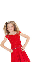 Tilt image of girl wearing red frock looking sideways with hands on hips over white background