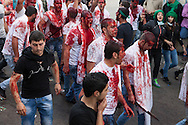 Shiite muslims, covered in their own blood, carrying swords and knives, marching through the streets of Nabatieh, Lebanon, commemorating the Day of Ashura (November 14, 2013). On Ashura Day, shiite muslims commemorate the death of Husayn Ibn Ali, grandson of the prophet Mohamed.