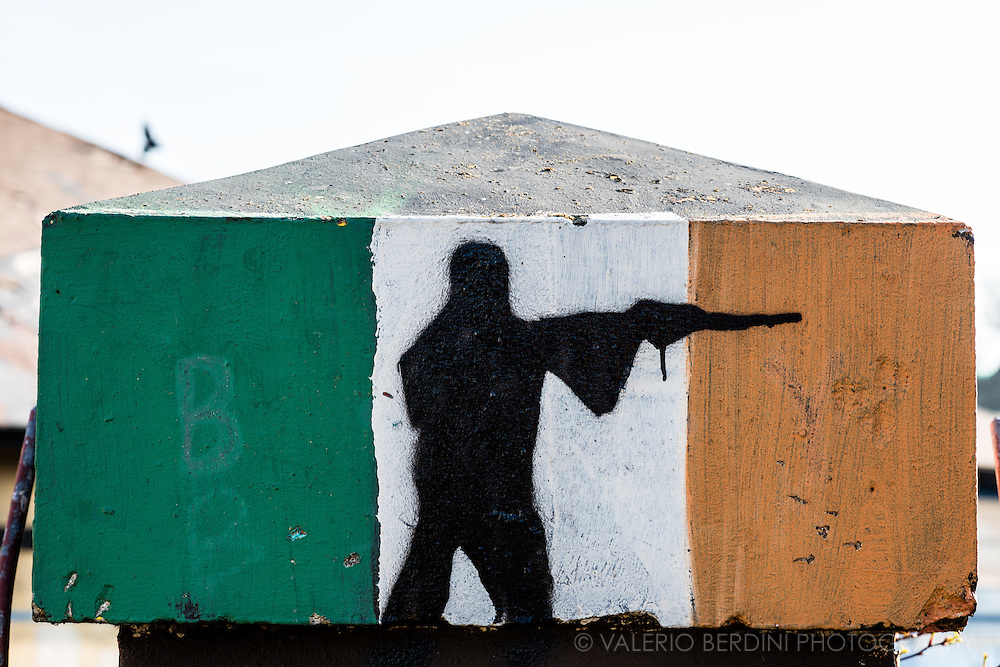 A man holding a gun is painted over an Irish flag in the Bogside, a neighbourhood outside the city walls of Derry. The area has always been a stronghold for dissident Republican activity.