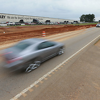 Motorist pass the Ashley Furniture factory as work continues on Hwy 15 in Ecru.