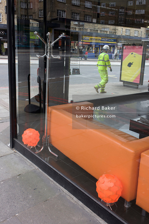 A workman walks past a retailer's window containing orange spheres and sofa.