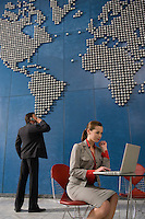 Business man using mobile phone business woman using laptop in office with world map on wall