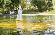 Model boats being sailed on park boating pond, Woodbridge, Suffolk, England, UK