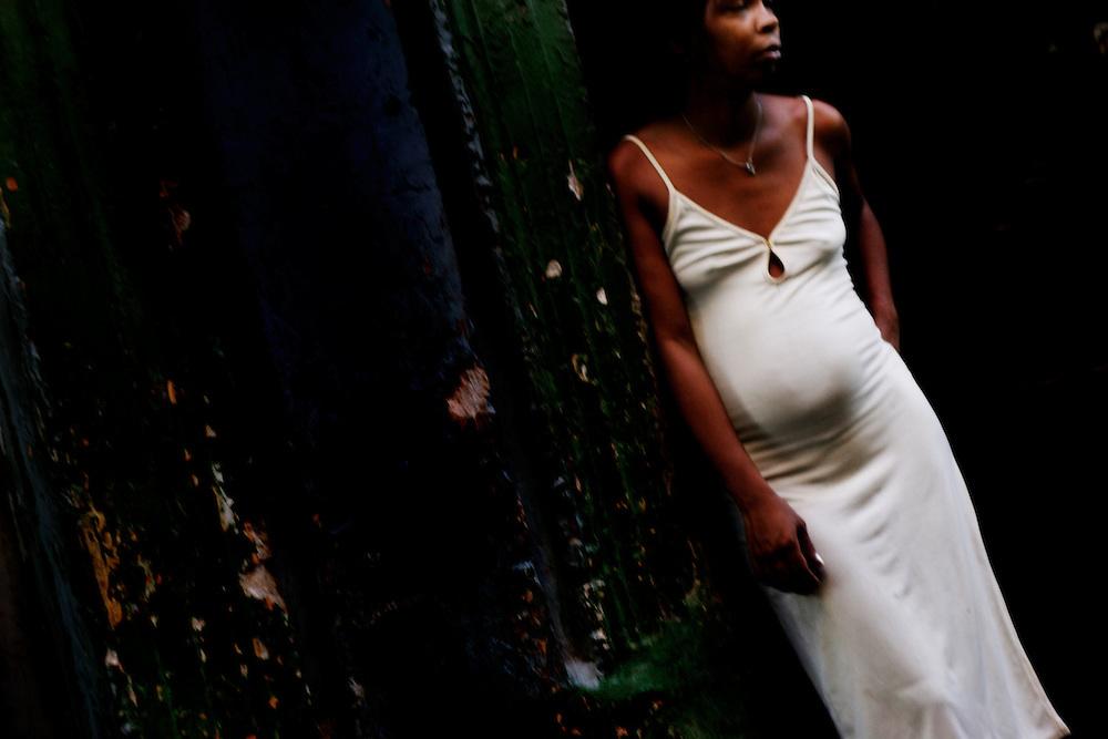 A woman in a white dress leans in a doorway in a street in Old Havana, Cuba.
