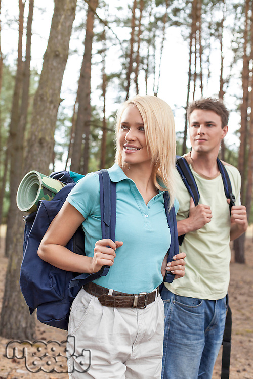 Young couple with backpacks trekking in forest