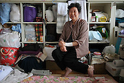 Kiyoi ABE, 65 ans, anciennement consultante pour kimonos, est à présent résidente du Centre par nécessité avant tout, mais aussi presque par choix. Ishinomaki est sa ville, elle ne veut pas la quitter ni quitter les amis quelle y a encore. Au centre de réfugiés, il existe une vie sociale qui fut éclatée le 11 mars. .Kiyoi Abe vit avec 11 autres personnes dans ce qui était une salle de classe. .Derrière elle et autour de son couchage sont rangés ces affaires. Elle conserve ce réveil jaune qui ne fonctionne plus et marque toujours lheure du passage du tsunami.