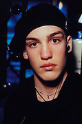 Teenager with ear piercing wearing black Kangol flatcap, Croatia, 1997.