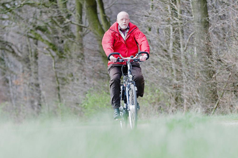 Deutschland , Ein Rentner auf einem Elektrofahrrad auf einem Waldweg   |  Germany, a man on an e-bike  is riding along on a rural road |