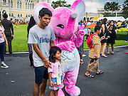09 JANUARY 2016 - BANGKOK, THAILAND: A man and his daughter pose with pink elephant mascot for Thai tourism during Children's Day festivities at Government House. National Children's Day falls on the second Saturday of the year. Thai government agencies sponsor child friendly events and the military usually opens army bases to children, who come to play on tanks and artillery pieces. This year Thai Prime Minister General Prayuth Chan-ocha, hosted several events at Government House, the Prime Minister's office.     PHOTO BY JACK KURTZ