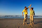 Couple playing around on beach, Queensland, N. Stradbroke Island, Australia