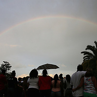 "A rainbow is seen over Lake Eola park during the ""National Moment of Silence"" event at the Lake Eola bandshell in downtown Orlando, Florida on Thursday, August 14, 2014. In light of the recent killing of eighteen year old Mike Brown in Ferguson, Missouri, citizens across America are gathering in solidarity to hold vigils and observe a moment of silence to honor victims of suspected police brutality. (AP Photo/Alex Menendez)"