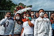 ITALY, Terzigno : Children wearing gas masks are seen in front of the entrance of the Terzigno dump on October 24, 2010. A flower crown, indicating the death of the Vesuvius national park, was left at the gates of the Terzigno landfill at the end of a rally..AFP PHOTO / ROBERTO SALOMONE