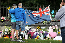 March 18, 2019 - Christchurch, New Zealand - People pay their respects at a memorial outside the Botanical Gardens as a tribute to victims of the mosque attacks in Christchurch on March 17, 2019. At least 50 people were killed and 36 injured in mass shootings at two mosques in the New Zealand city of Christchurch Friday, 15 March. A 28-year-old Australian born man appeared in Christchurch District Court on Saturday charged with murder. (Credit Image: © Sanka Vidanagama/NurPhoto via ZUMA Press)