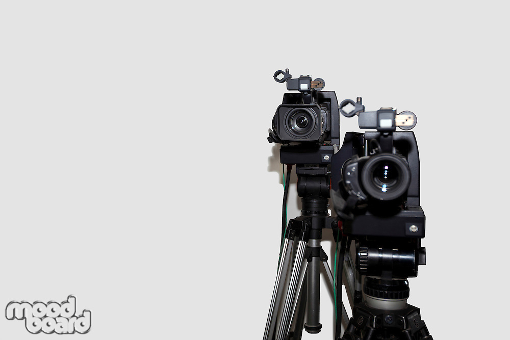 Camera and tripod against white background