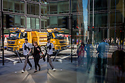 City street corner plate glass reflection and passing Londoners and yellow construction lorry.
