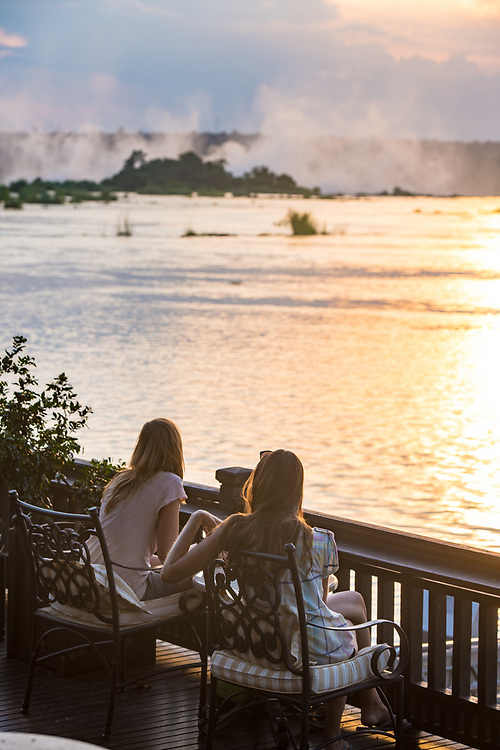 Two young women sit on the sundeck of the Royal Livingston Hotel and watch the sun set over the Zambezi River Livingstone, Zambia