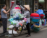 A Vietnamese woman selling housewares from a bicycle in the Old Quarter, Hanoi, Vietnam, Southeast Asia