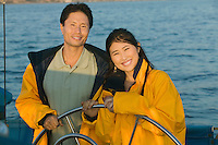 Couple wearing yellow anoraks at steering wheel of sailboat (portrait)