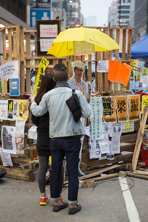 A couple reads a hand-written sign hanging on a barricade at the Occupy Mongkok protest site. Protesters known as the Umbrella Revolution or Occupy Mongkok, an extension of the larger Occupy Central movement, have taken over a number of blocks on the busy road and staged an ongoing demonstration calling for universal suffrage for Hong Kong.